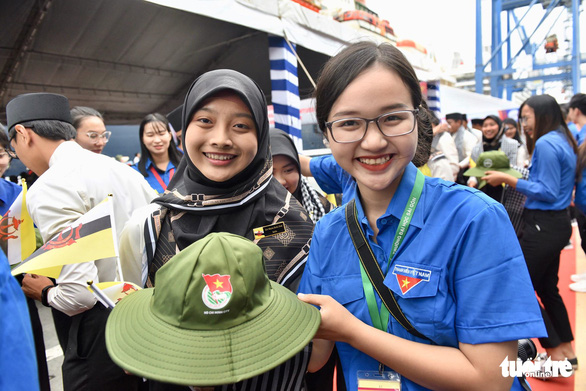 A young Vietnamese woman presents a cap to a Bruneian delegate of the SSEAYP 2019. Photo: Duyen Phan / Tuoi Tre