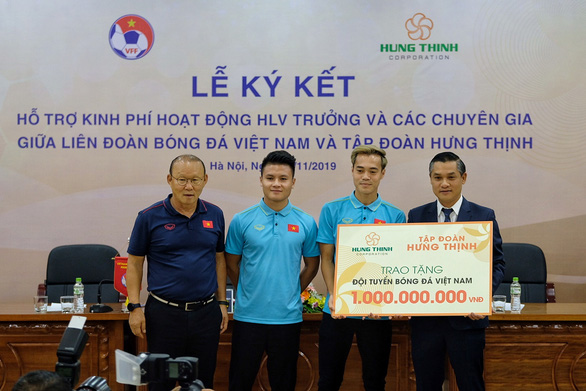 Nguyen Van Cuong (R) gives VND1 billion ($43,136) to the Vietnamese national football team. Photo: Nam Tran / Tuoi Tre