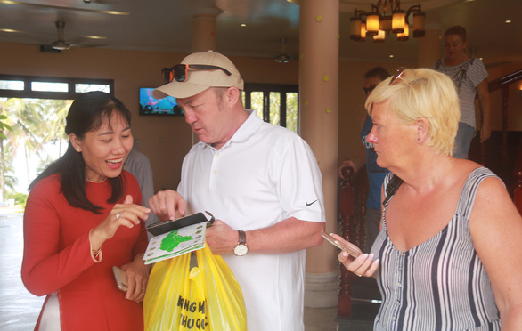 A female tour guide talks to two foreign visitors at an attraction in Phu Quoc Island, Kien Giang Province, Vietnam. Photo: Khoa Nam / Tuoi Tre
