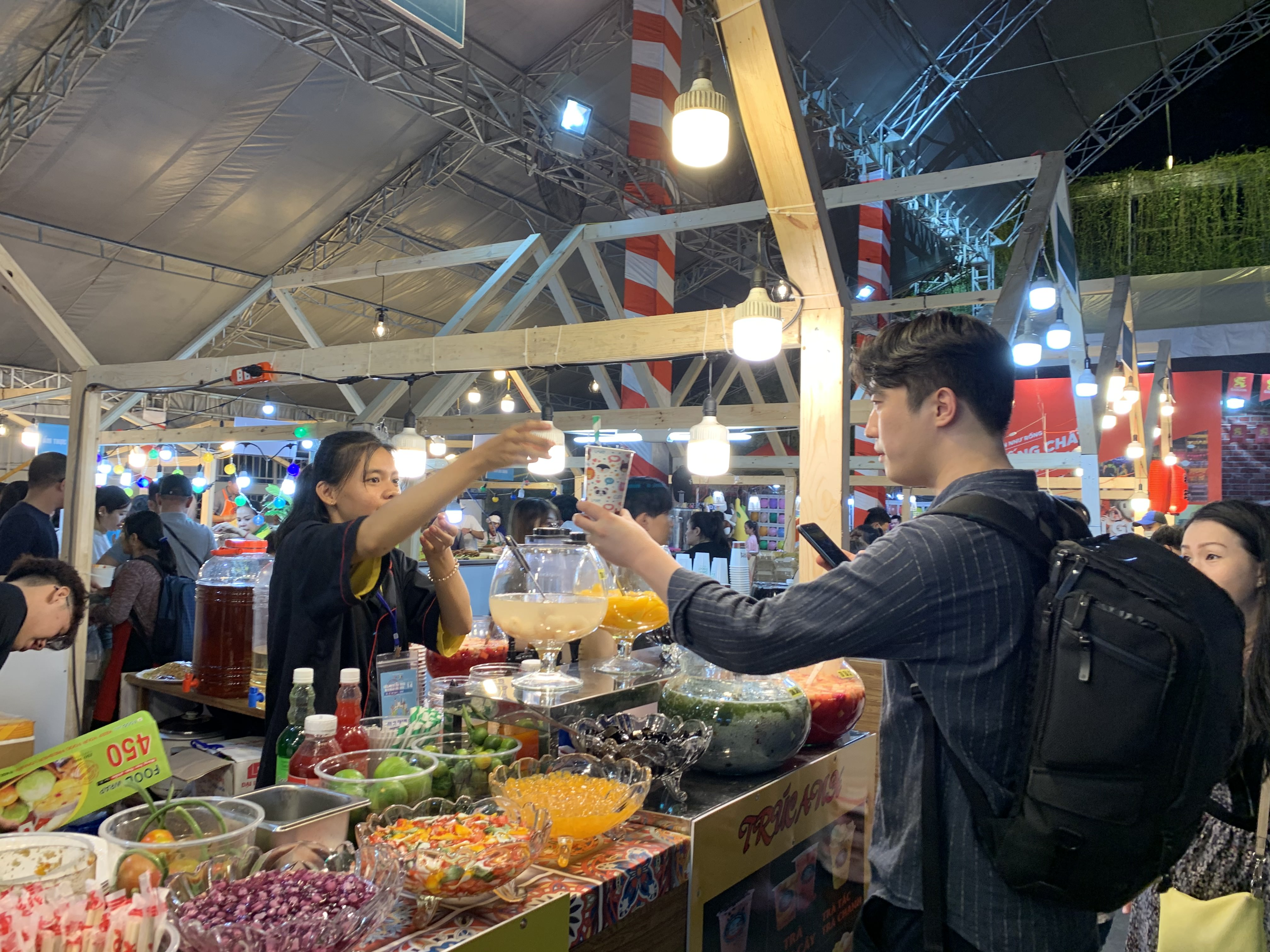 A South Korean visitor buys a drink from a stall at the international food festival held at the Youth Cultural House in District 1, Ho Chi Minh City, November 14, 2019. Photo: Bao Anh / Tuoi Tre News