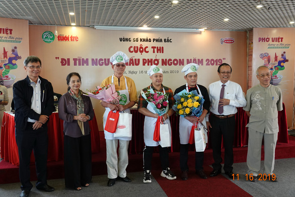 Three finalists receive gifts and flowers at the qualification round of a cooking contest searching for the best pho chefs in Vietnam held in Hanoi, November 16, 2019. Photo: Ngoc Quang / Tuoi Tre