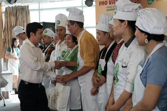 The organizer presents gifts to contestants at the qualification round of a cooking contest searching for the best pho chefs in Vietnam held in Hanoi, November 16, 2019. Photo: Mai Thuong / Tuoi Tre
