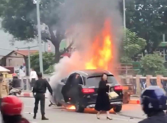 A woman wearing a black dress and high heels is seen next to the Mercedes car and motorbike burning in the incident in Cau Giay District, Hanoi, Novembr 20, 2019. Photo: Tuoi Tre contributor