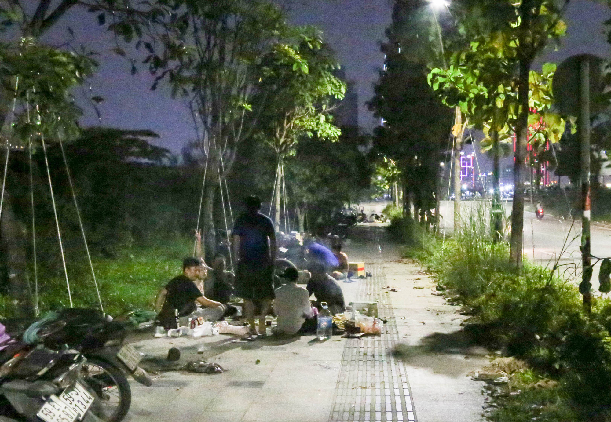 <em>Groups of people eat and drink on the sidewalk. Photo: </em>Thao Le / Tuoi Tre