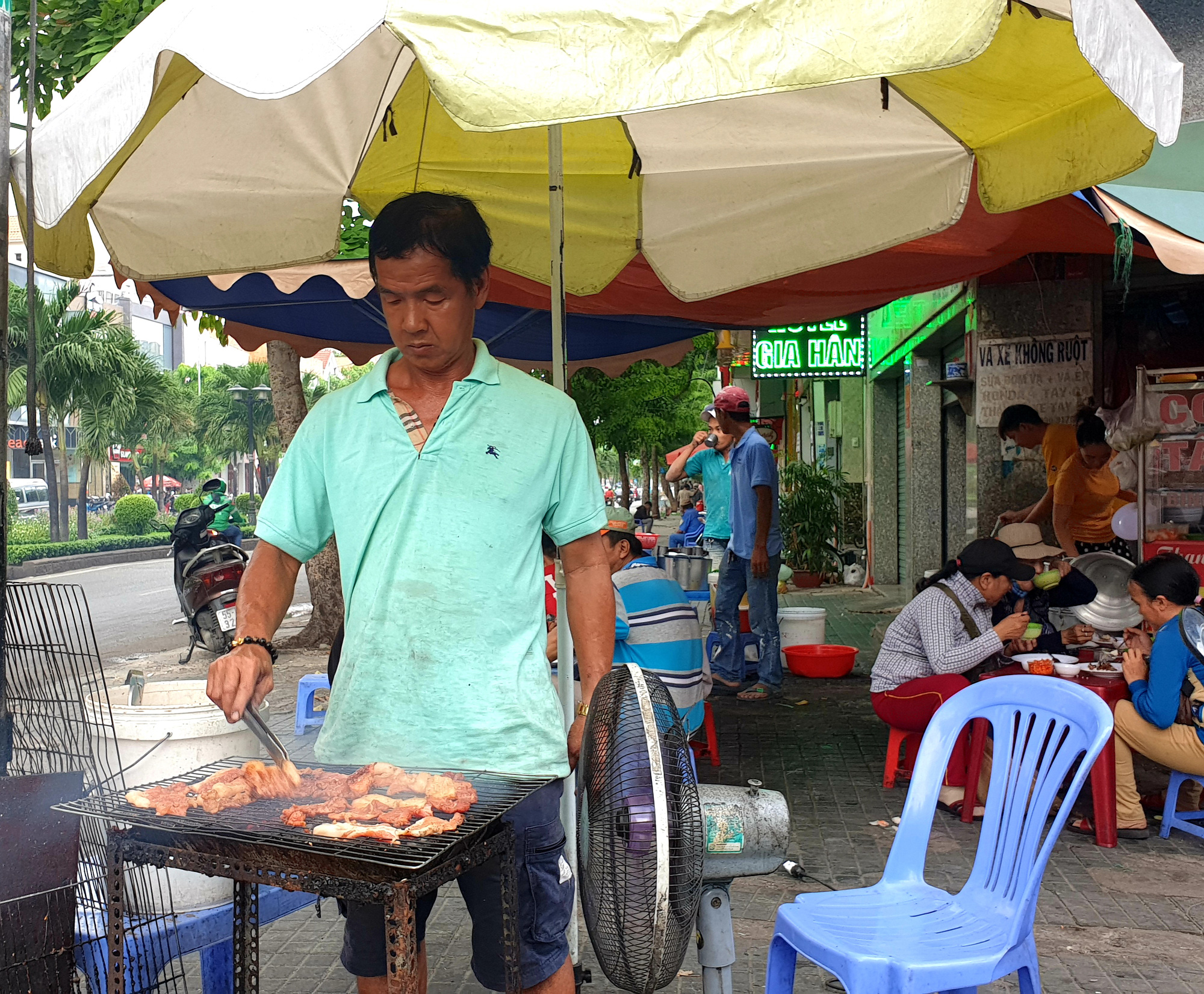A man grills pork to serve with broken rice at a diner in Ho Chi Minh City. Photo: Bong Mai / Tuoi Tre