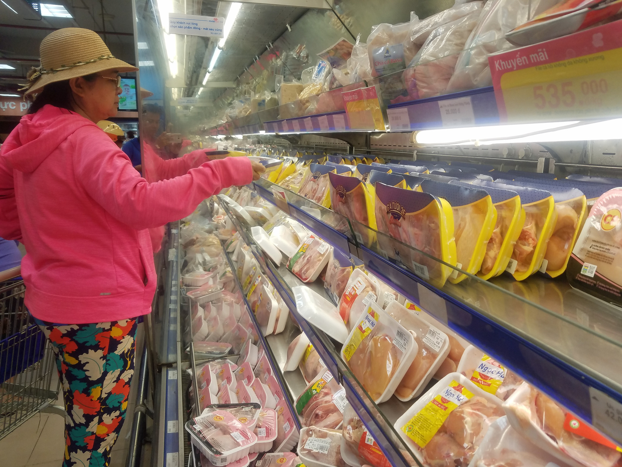 A woman browses for chicken to replace pork in her daily meals. Photo: Nguyen Tri / Tuoi Tre