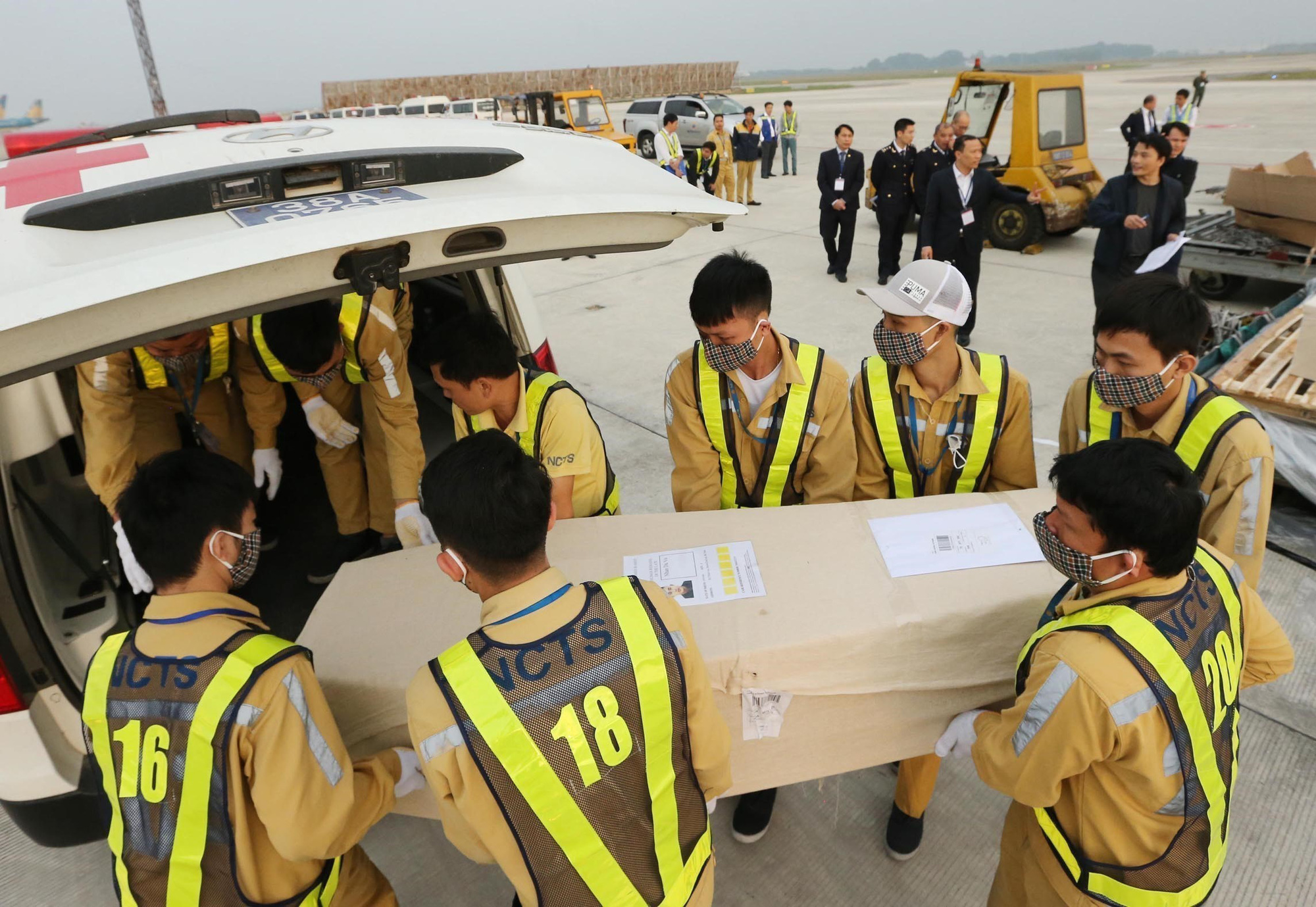 Airport employees carry coffins containing the bodies of 16 Essex truck victims to ambulances. Photo: Vietnam News Agency