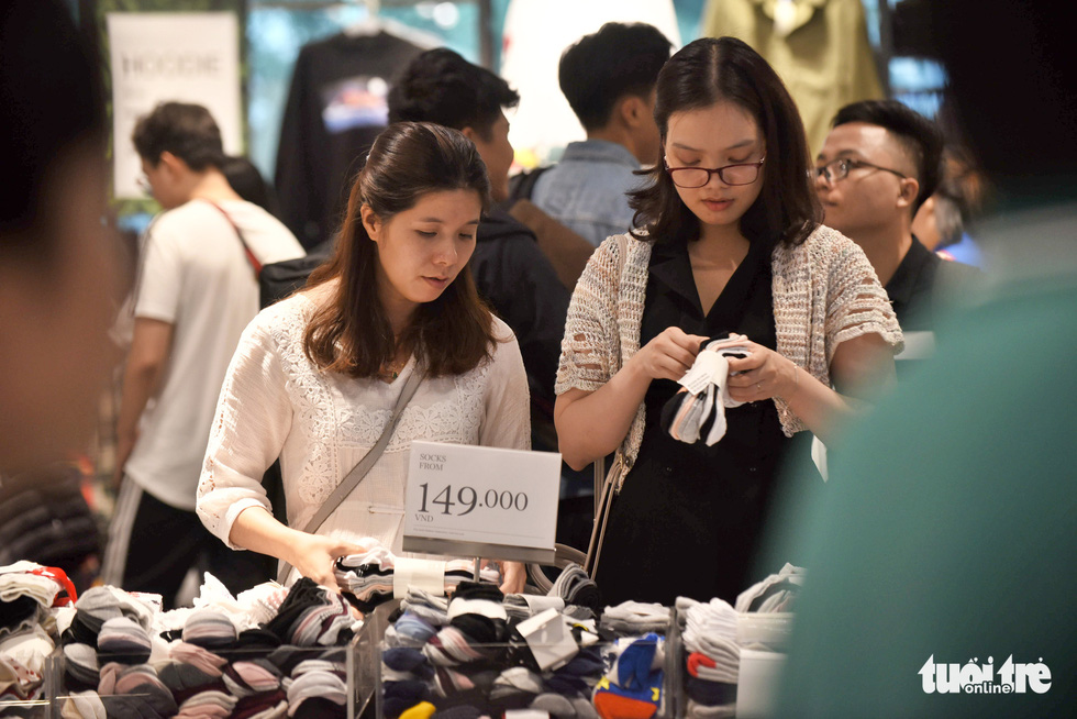 Two women shop for socks at a store inside Vincom Center in District 1, Ho Chi Minh City on November 29, 2019. Photo: Duyen Phan / Tuoi Tre