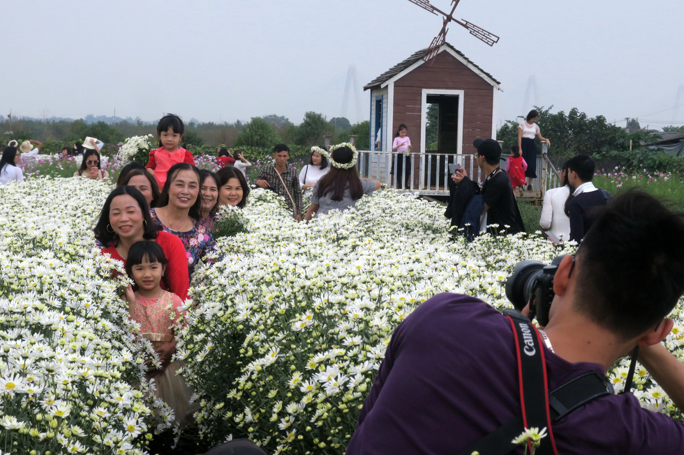 Women pose for a photo with daisies in Hanoi. Photo: T.T.D. / Tuoi Tre