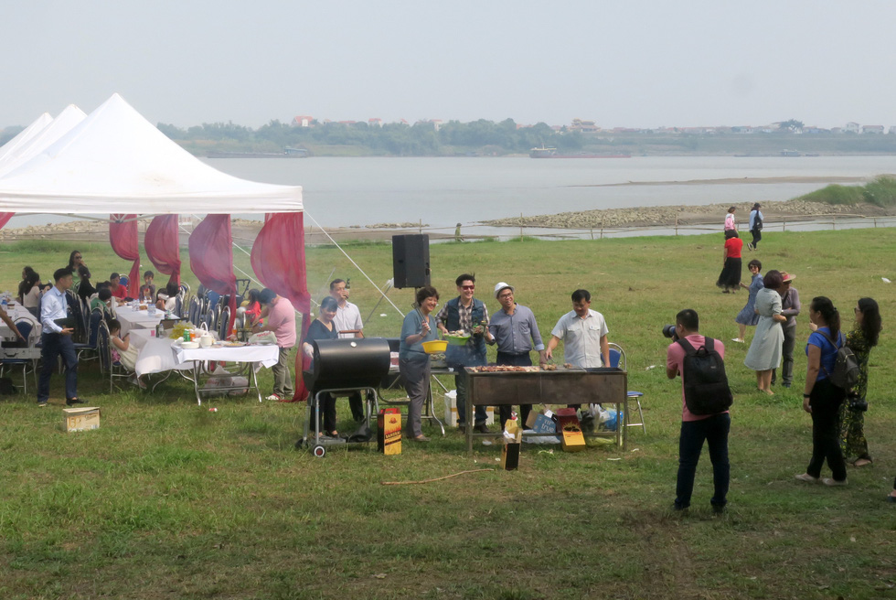 A family organizes a barbecue at a daisy field in Hanoi. Photo: T.T.D. / Tuoi Tre