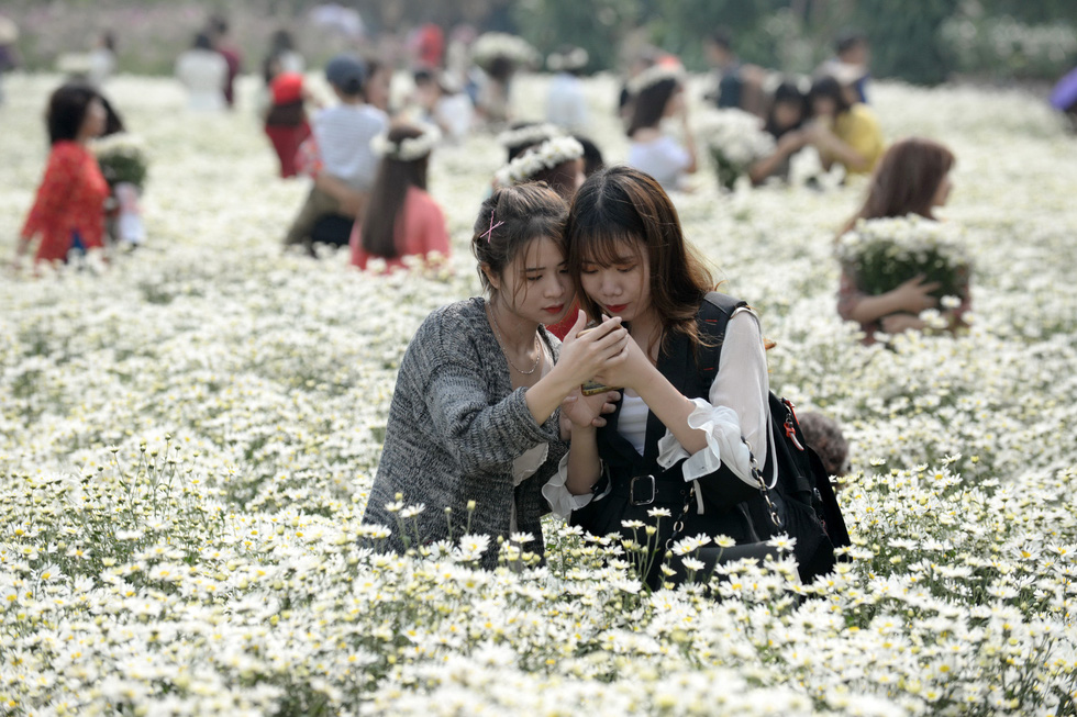 Two young women take a selfie with daisies in Hanoi. Photo: T.T.D. / Tuoi Tre