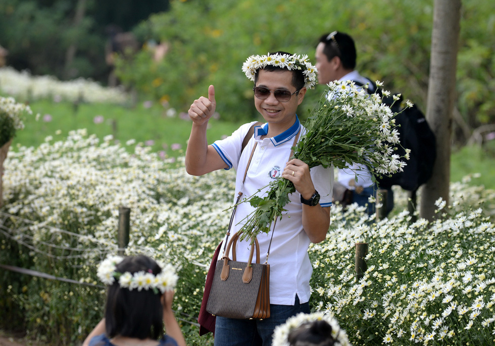 A man poses for a photo with daisies in Hanoi. Photo: T.T.D. / Tuoi Tre