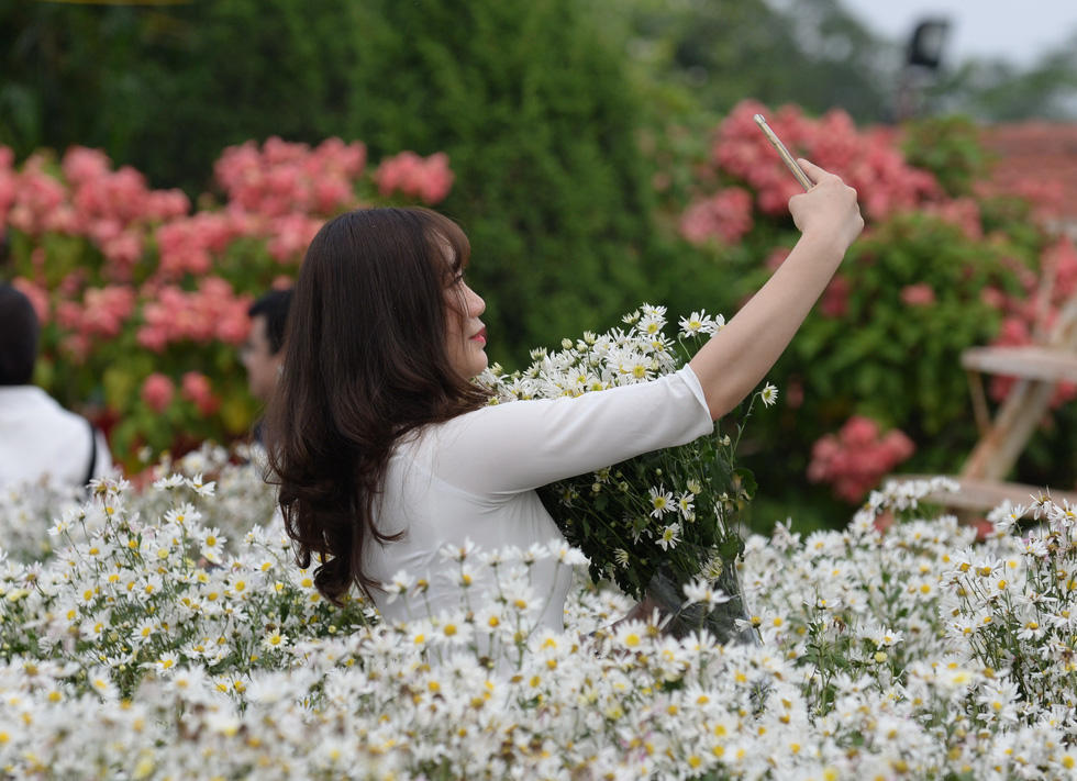 A young woman takes a selfie with daisies in Hanoi. Photo: T.T.D. / Tuoi Tre