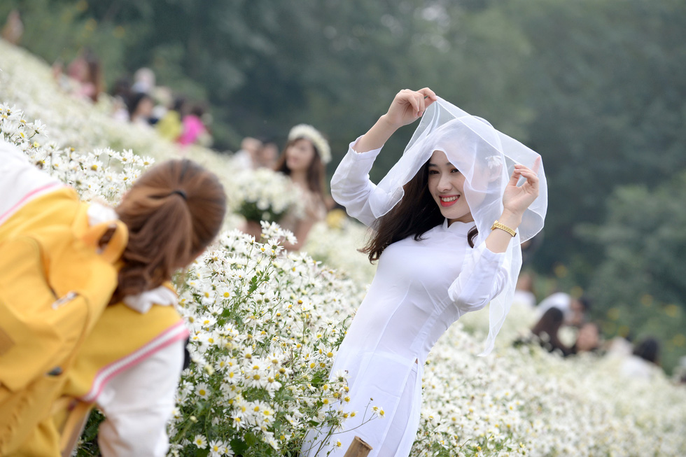 A young woman poses for a photo with daisies in Hanoi. Photo: T.T.D. / Tuoi Tre