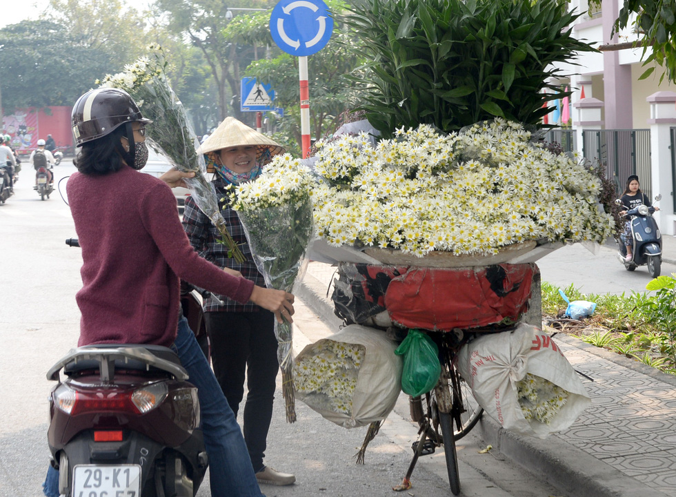A woman sells daisies carried on her bike in Hanoi. Photo: T.T.D. / Tuoi Tre