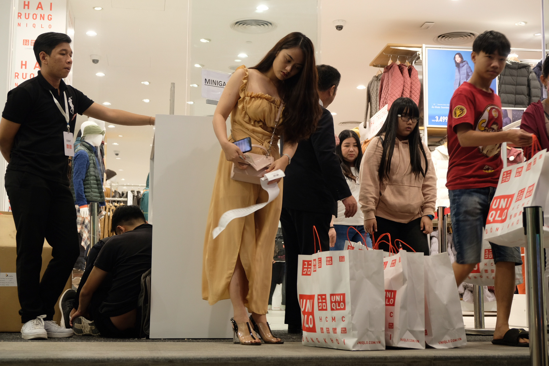 A woman leaves the store with multiple shopping bags. Photo: Bong Mai / Tuoi Tre