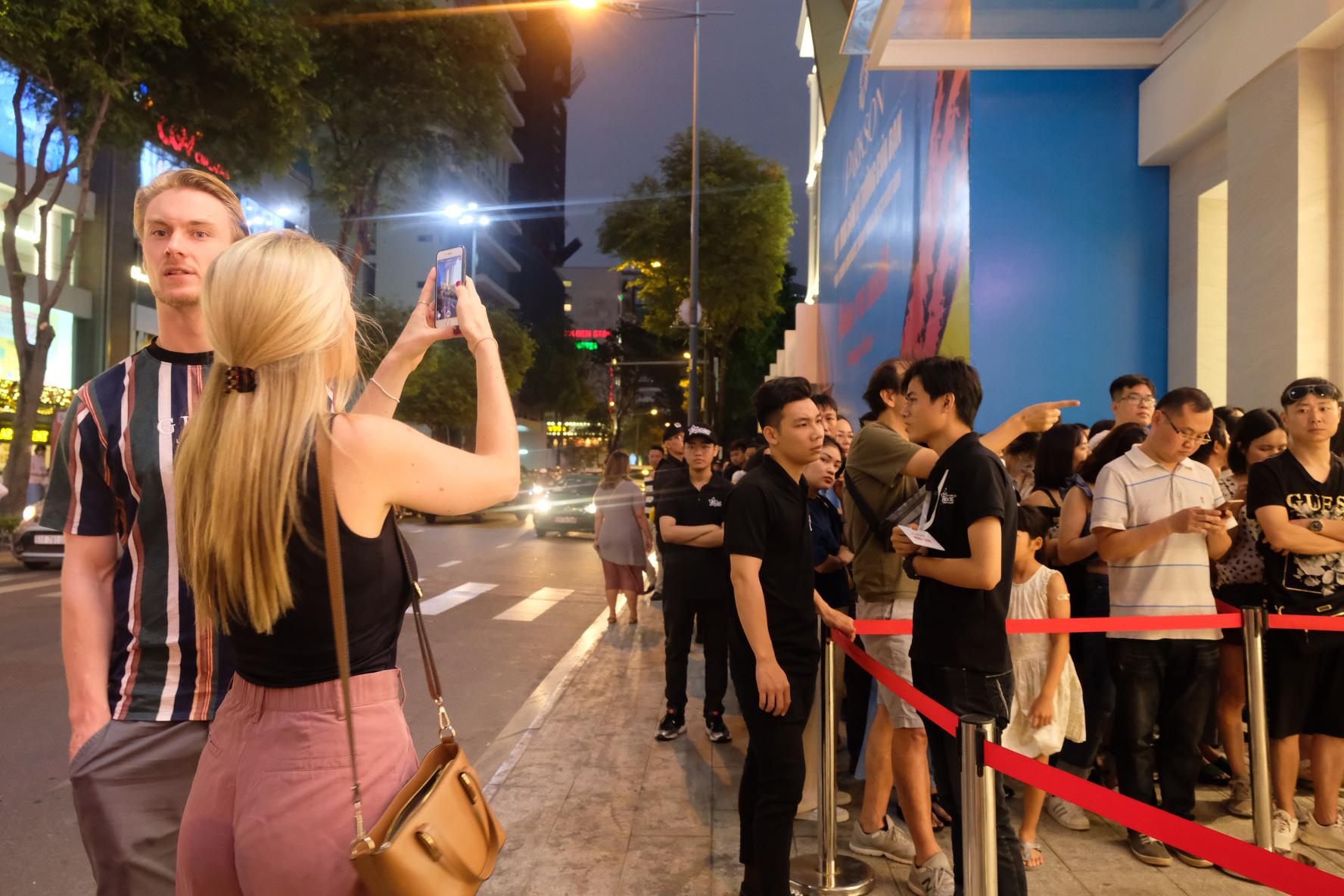 Foreigner tourists take photos of the queue line. Photo: Bong Mai / Tuoi Tre