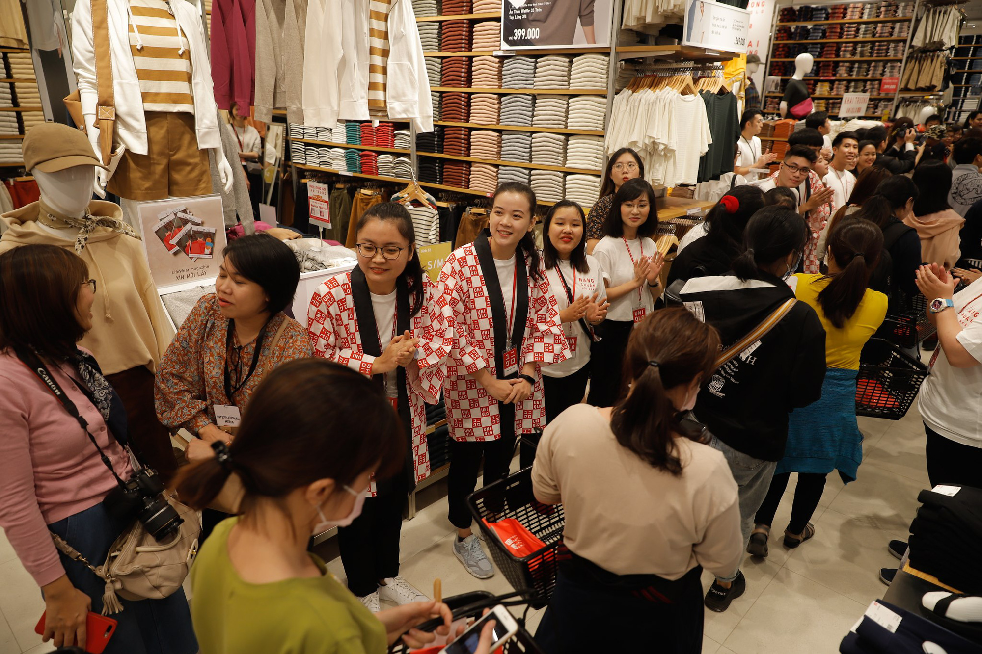 Employees hand shopping baskets to customers inside the store. Photo: Nguyen Tri / Tuoi Tre