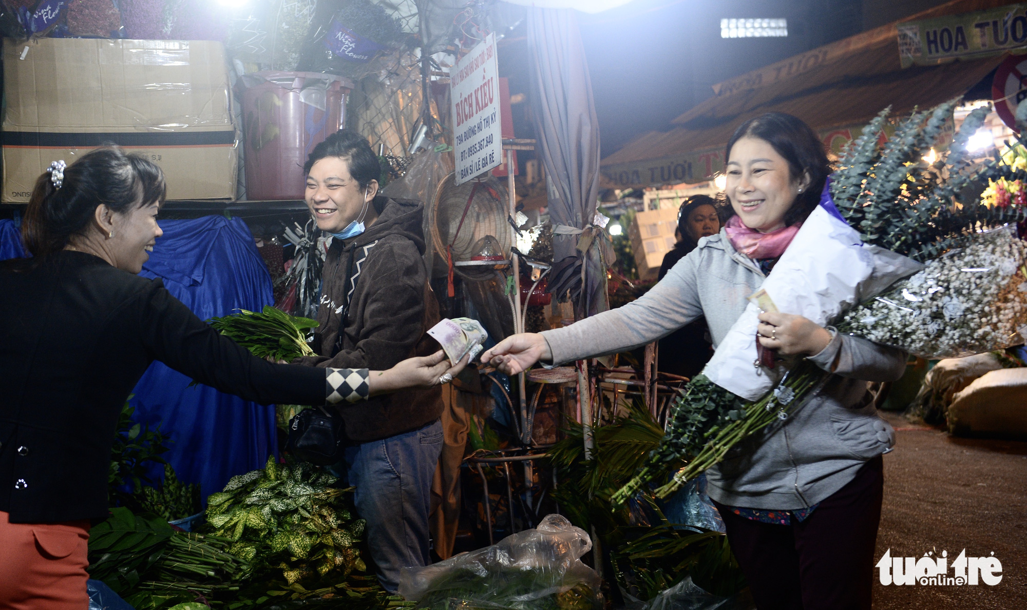 A woman buys flowers at a market in the early morning in Ho Chi Minh City. Photo: Tu Trung / Tuoi Tre