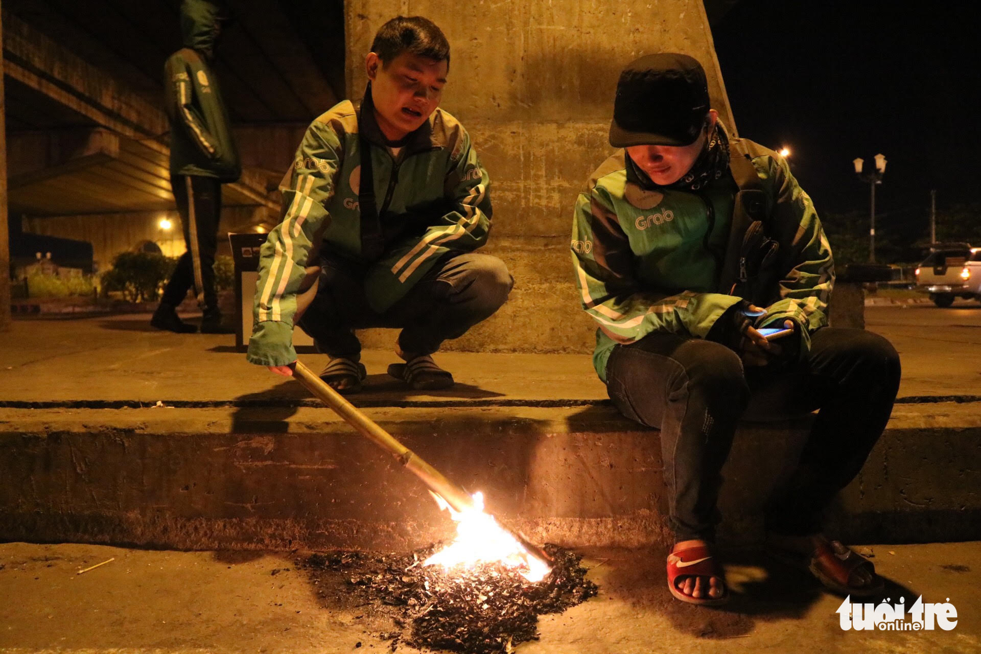 Two GrabBike drivers light a small fire to warm themselves under an overpass in Thu Duc District, Ho Chi Minh City. Photo: Hoang An / Tuoi Tre