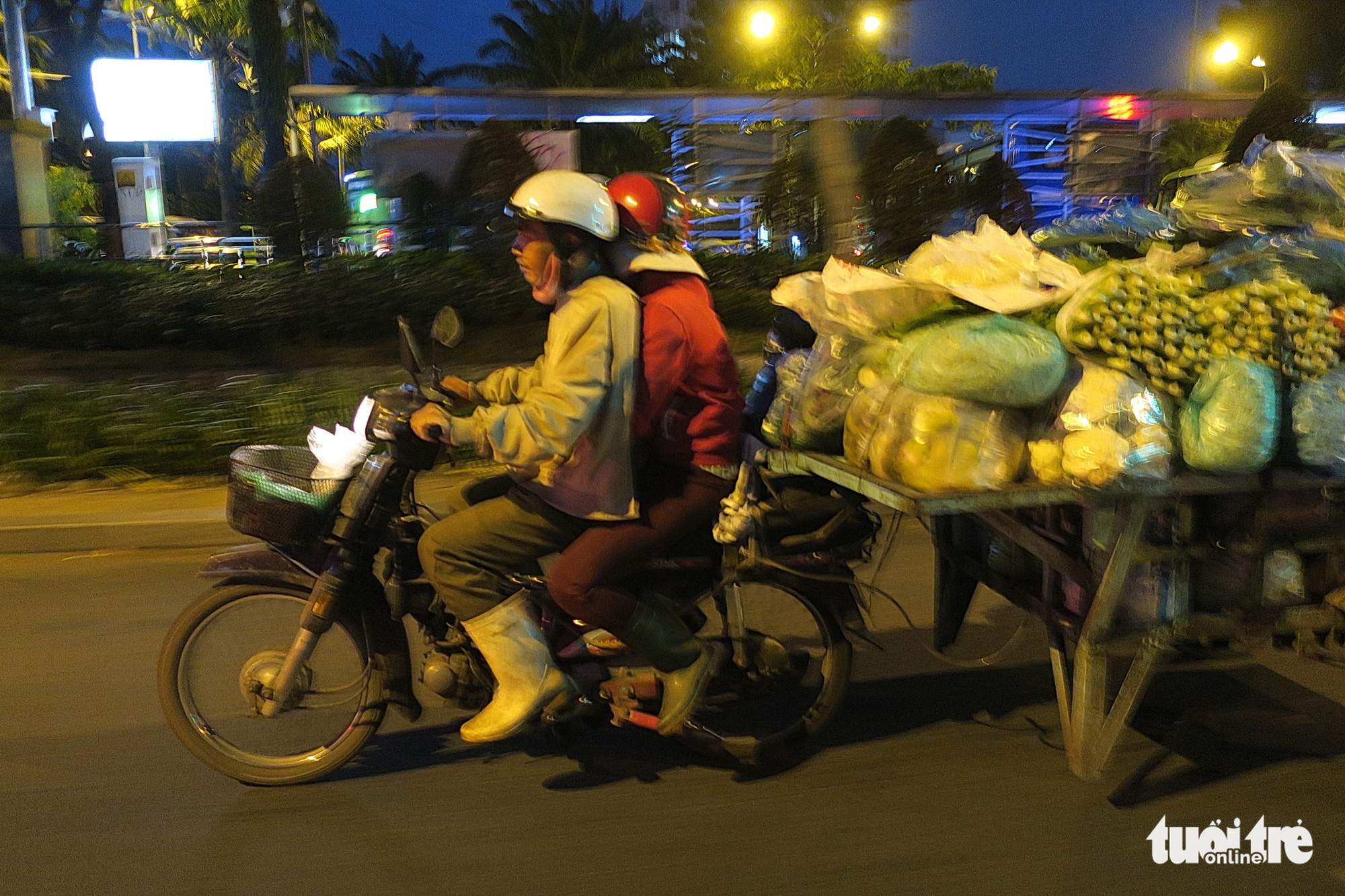 A married couple transports vegetables from a wholesale market to buyers in the downtown area in Ho Chi Minh City. Photo: T.T.D. / Tuoi Tre