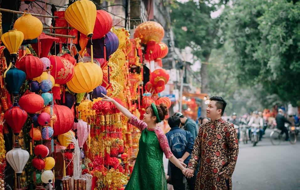A couple wanders around Hanoi street on Tet holiday.