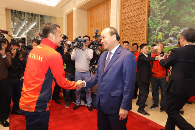 Vietnam's Prime Minister Nguyen Xuan Phuc (R) and the U22 men's football team member Trong Hoang shake hands at the Government Office in Hanoi on December 11, 2019. Photo: Viet Dung / Tuoi Tre
