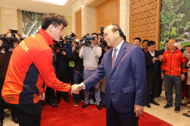 Vietnam's Prime Minister Nguyen Xuan Phuc (R) and the U22 men's football team member Tan Sinh shake hands at the Government Office in Hanoi on December 11, 2019. Photo: Viet Dung / Tuoi Tre