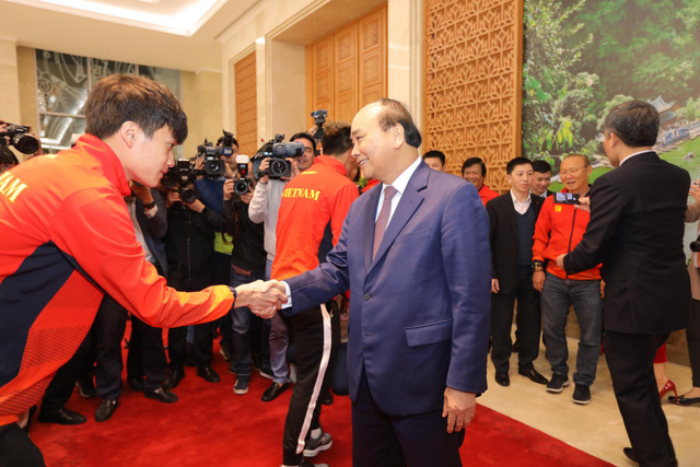Vietnam's Prime Minister Nguyen Xuan Phuc (R) and the U22 men's football team member Hoang Duc shake hands at the Government Office in Hanoi on December 11, 2019. Photo: Viet Dung / Tuoi Tre
