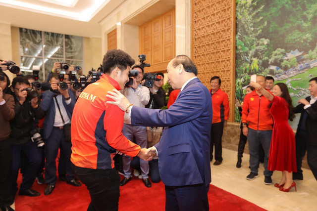 Vietnam's Prime Minister Nguyen Xuan Phuc (R) and the U22 men's football team member Duc Chinh shake hands at the Government Office in Hanoi on December 11, 2019. Photo: Viet Dung / Tuoi Tre