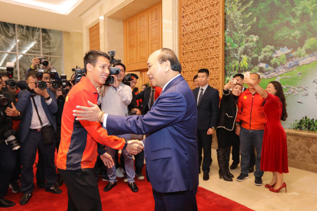 Vietnam's Prime Minister Nguyen Xuan Phuc (R) and the U22 men's football team captain Hung Dung shake hands at the Government Office in Hanoi on December 11, 2019. Photo: Viet Dung / Tuoi Tre