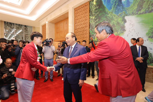Vietnam's Prime Minister Nguyen Xuan Phuc and the national women's football team member Nguyen Bich Thuy shake hands at the Government Office in Hanoi on December 11, 2019. Photo: Viet Dung / Tuoi Tre