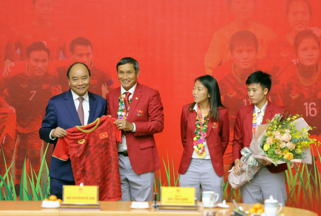 Prime Minister Nguyen Xuan Phuc (L) honors head coach Mai Duc Chung (2nd left) of the national women's football team and the players at a reception in Hanoi, December 11, 2019. Photo: Viet Dung / Tuoi Tre