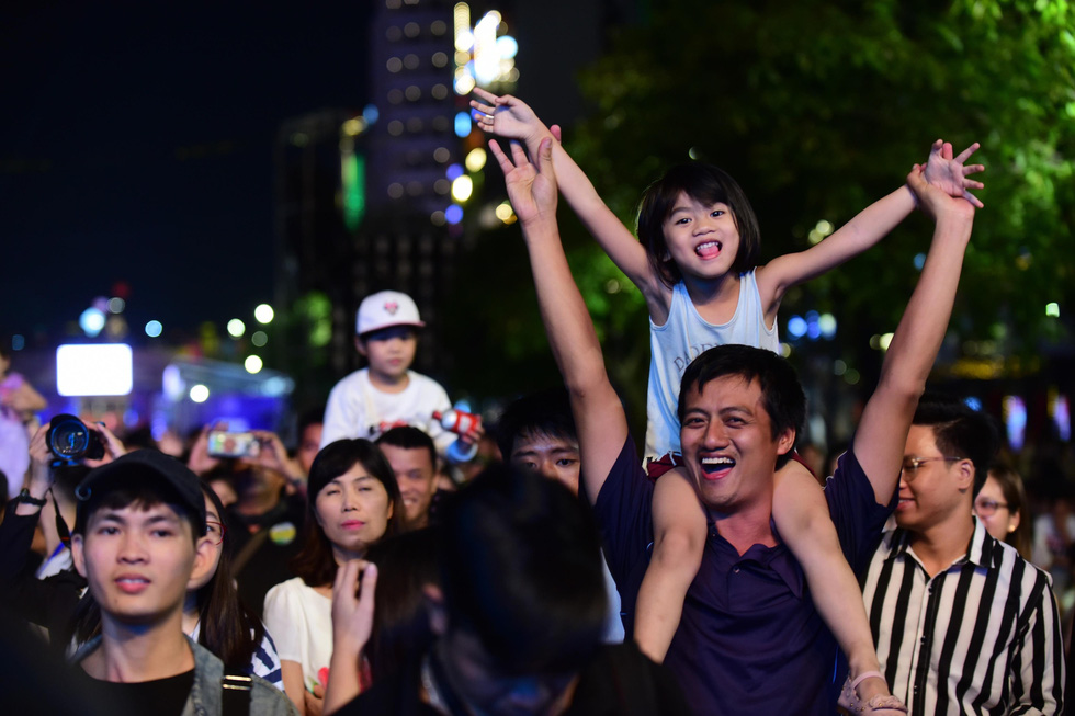 A father shoulders his daughter while enjoying performances at the inaugural Ho Chi Minh City International Music Festival on Nguyen Hue Walking Street in District 1 on December 13, 2019. Photo: Quang Dinh / Tuoi Tre