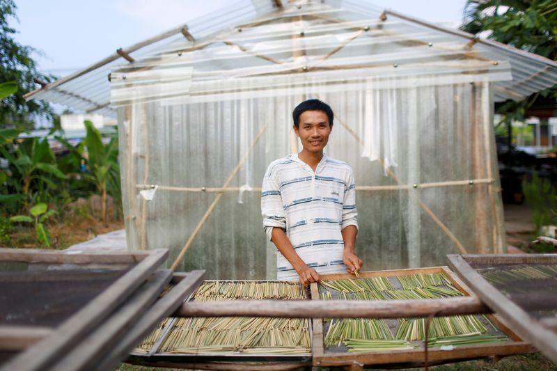 Tran Minh Tien, owner of 3T shop that makes grass straws, poses for a portrait in front of his workshop in Long An province. Photo: Reuters