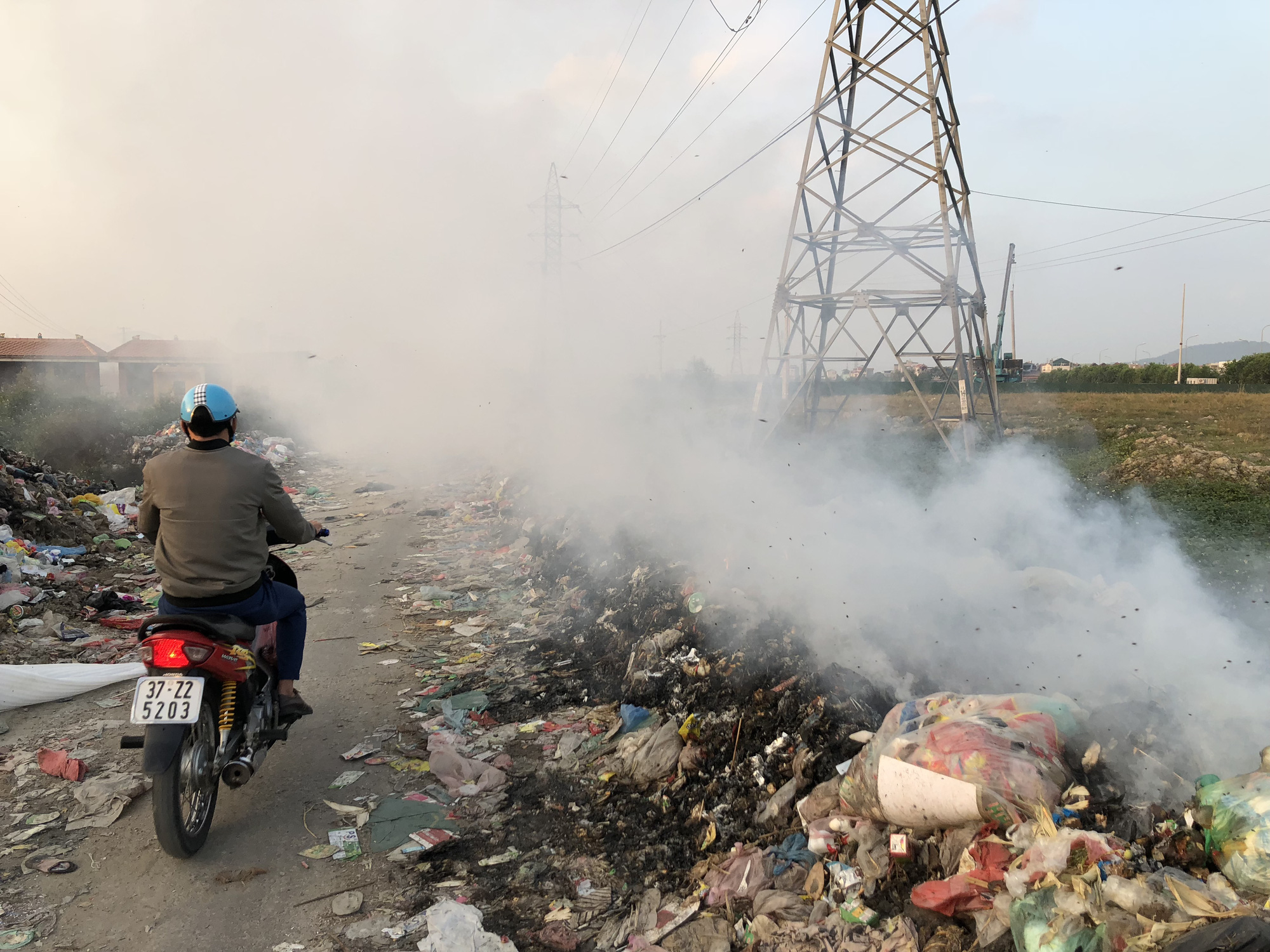 A man rides his bicycle along 'garbage street.' Photo: Quang The / Tuoi Tre