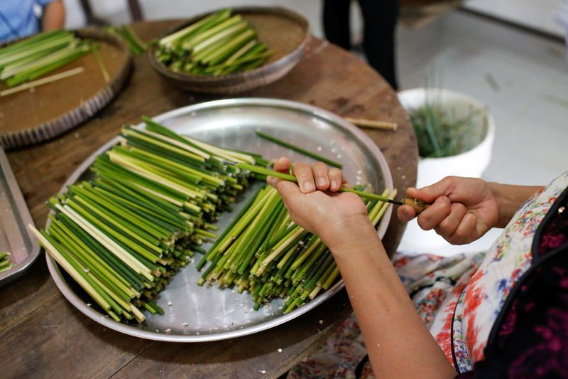 A worker makes straws from grass at the 3T workshop in Long An province. Photo: Reuters