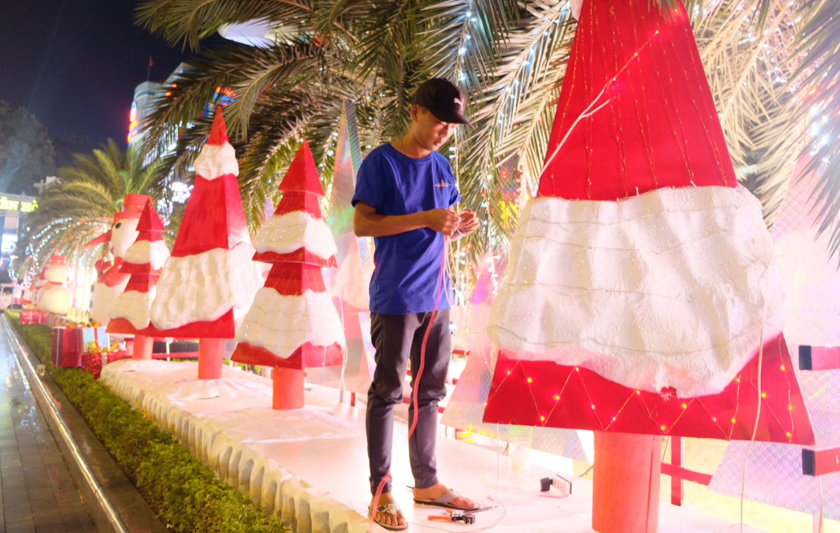 A man puts up Christmas decorations in Ho Chi Minh City. Photo: Bong Mai / Tuoi Tre
