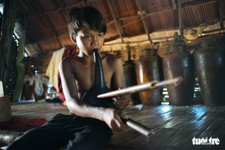 Dieu K'Soi, a 14-year-old boy of the Ma ethnic group playing a local instrument, is featured in a photo on display at an outdoor exhibition in Da Lat in the Central Highlands of Lam Dong. Photo: M. Vinh / Tuoi Tre