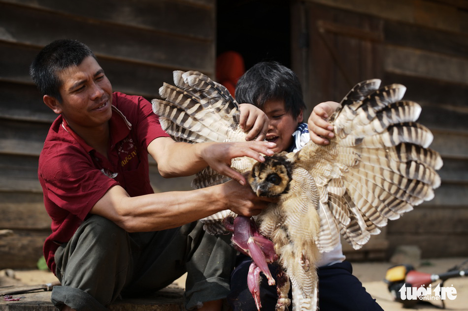 A man and his son killing a bird for house decoration as per an indigenous custom are featured in a photo on display at an outdoor exhibition in Da Lat in the Central Highlands of Lam Dong. Photo: M. Vinh / Tuoi Tre