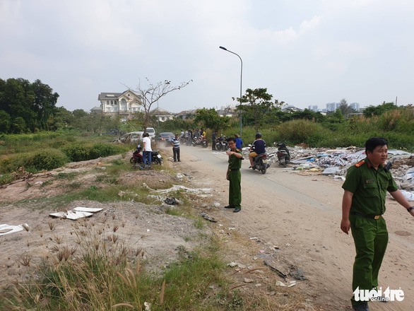 Police officers work at the scene near Thu Thiem Bridge in District 2, where a car was found burned in conjunction with a robbery-murder in District 7, Ho Chi Minh City, December 21, 2019. Photo: Minh Hoa / Tuoi Tre