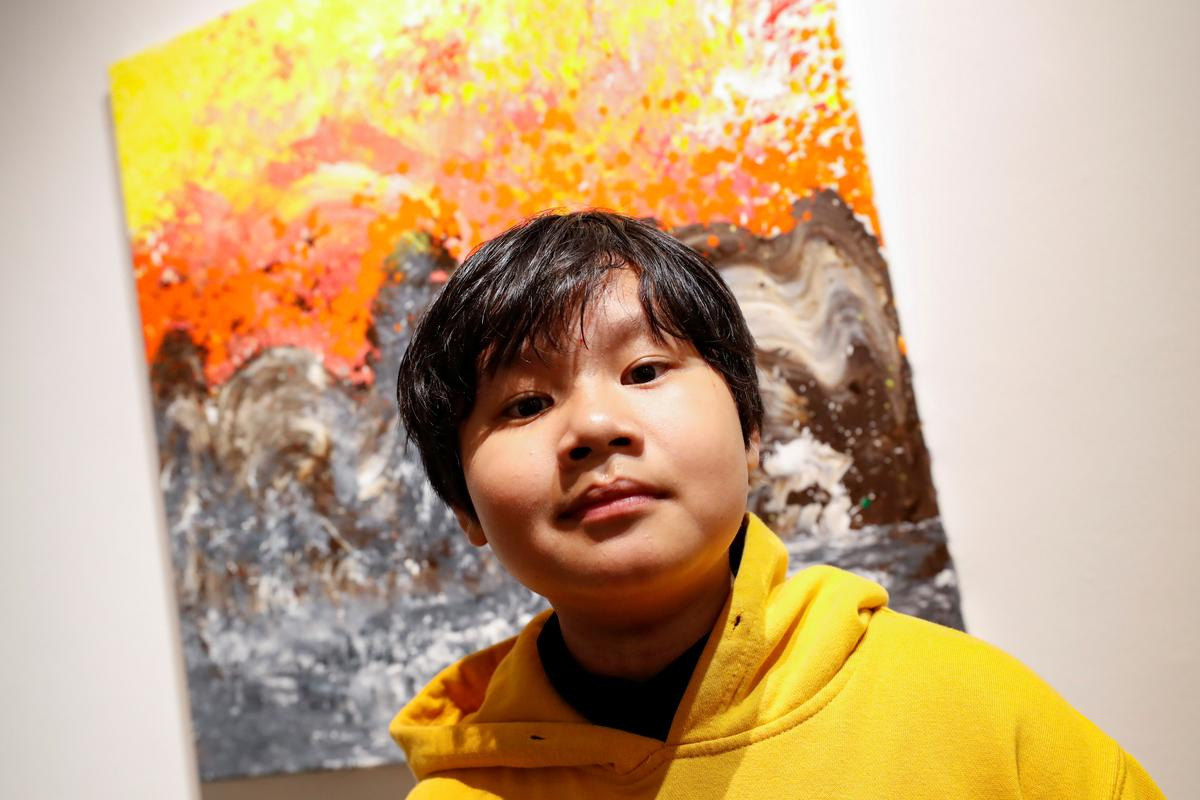 Xeo Chu, a Vietnamese art prodigy, poses in front of one of his pieces before his debut solo exhibition at the Georges Berges Gallery in New York City, New York, U.S., December 18, 2019.  Photo: Reuters