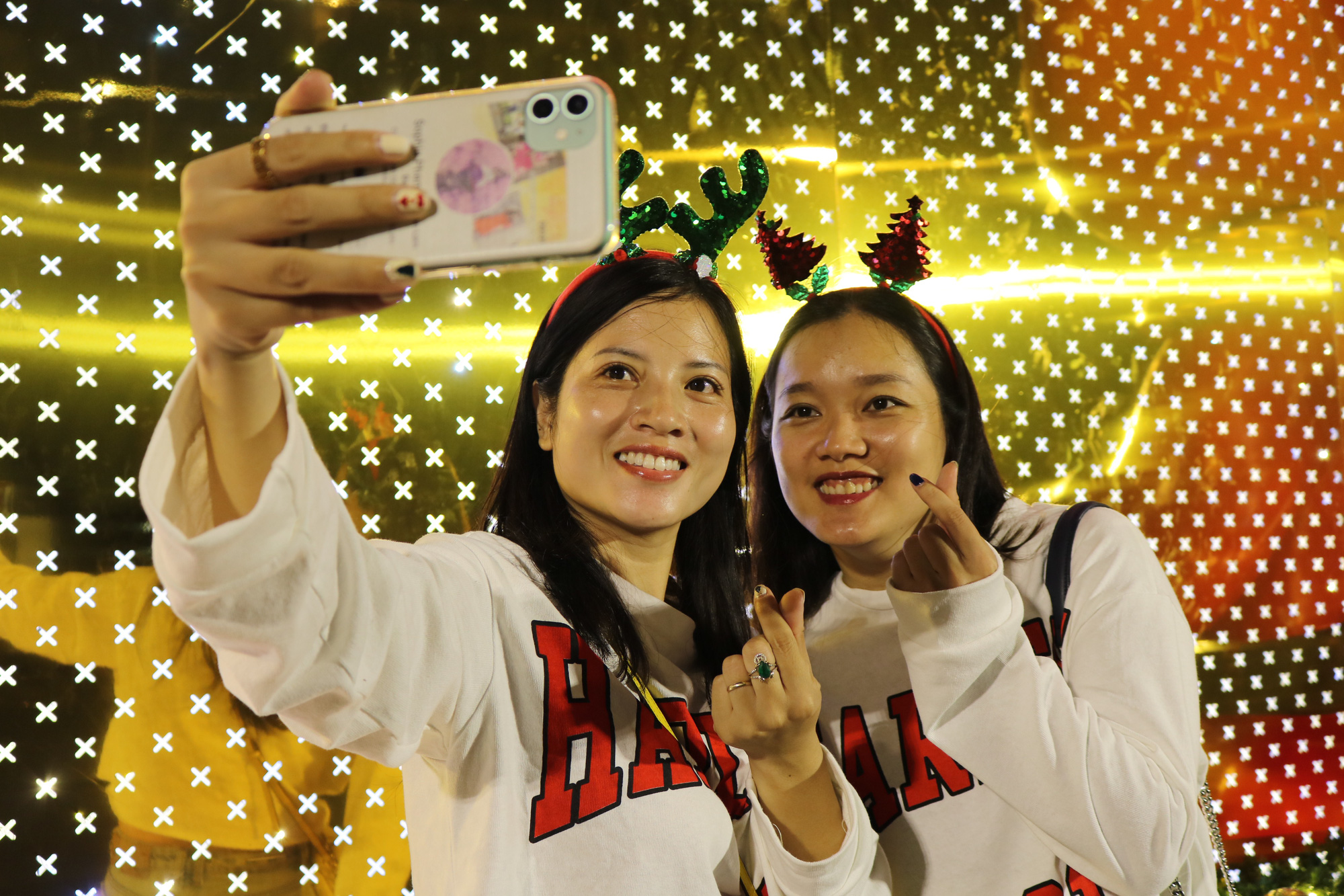 Two girls take a selfie in front of Landmark 81 Tower in Binh Thanh District. Photo: Hoang An / Tuoi Tre