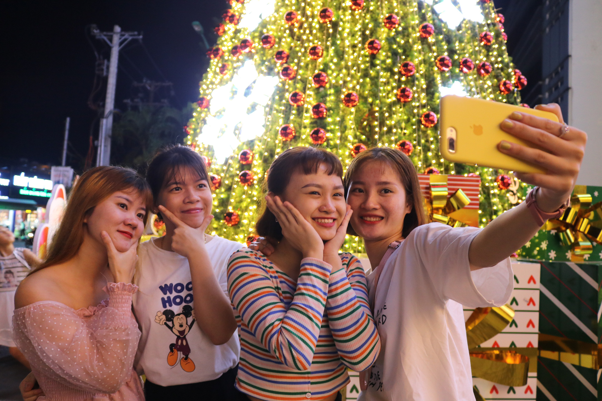 Young girls take a photo with the giant Christmas tree at Landmark 81 Tower. Photo: Hoang An / Tuoi Tre