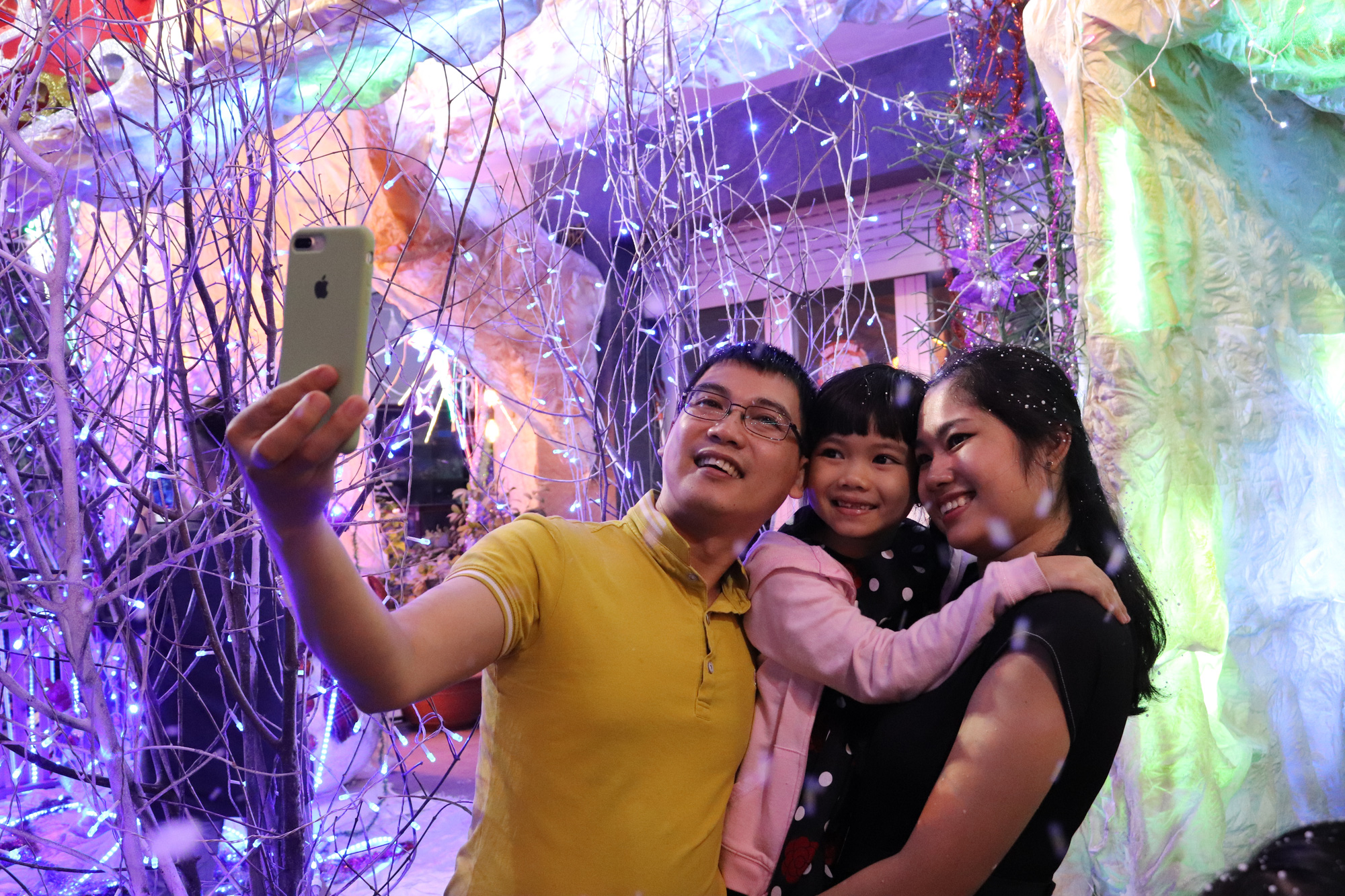 A family takes a photo at a Christian neighborhood in District 8. Photo: Khanh Tran / Tuoi Tre