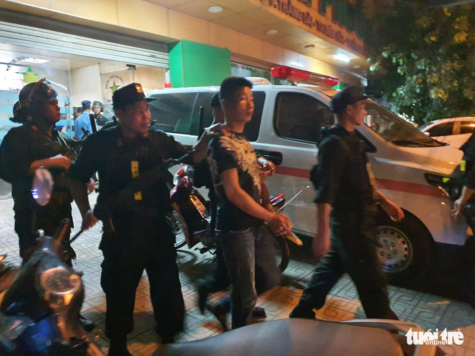 A suspect is escorted out of the hospital. Photo: S.D / Tuoi Tre