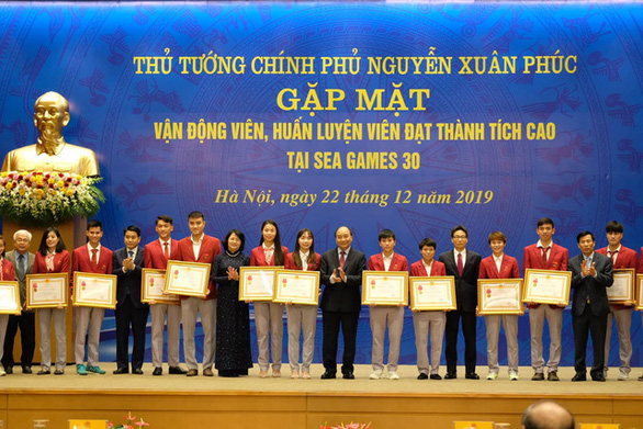 Prime Minister Nguyen Xuan Phuc (8th right) honors members of the Vietnamese sports delegation to the SEA Games 2019 with congratulatory certificates at the Government Office in Hanoi on December 22, 2019. Photo: Nam Tran / Tuoi Tre