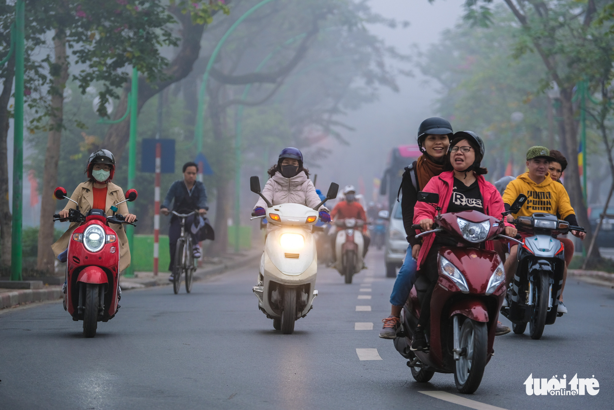 Commuters turn on their headlights in the foggy weather in Hanoi on December 24, 2019.