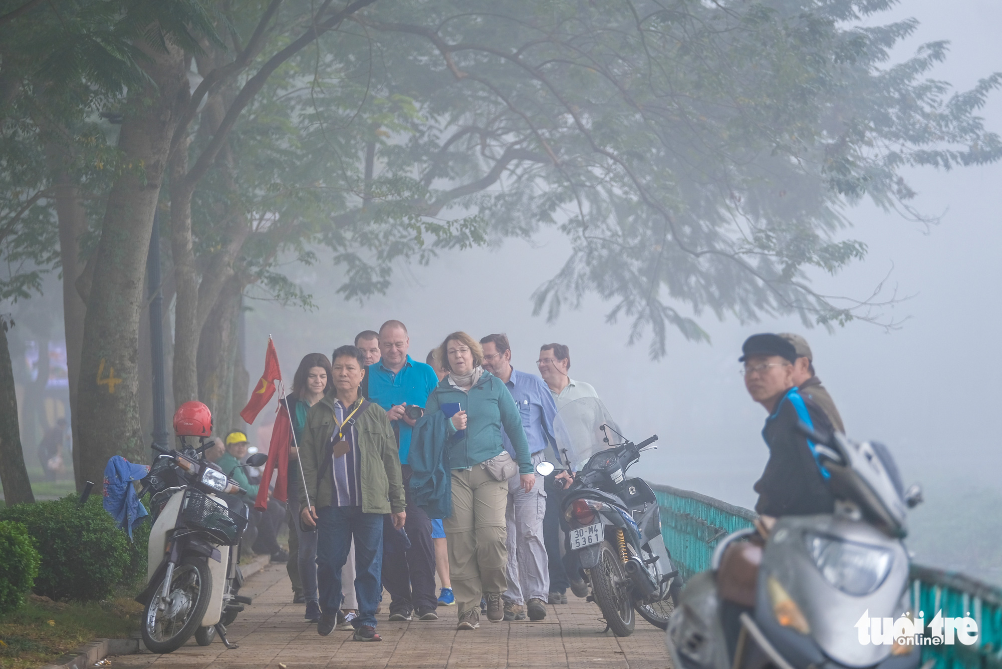 Foreign tourists walk along Ho Tay on a foggy morning in Hanoi on December 24, 2019.