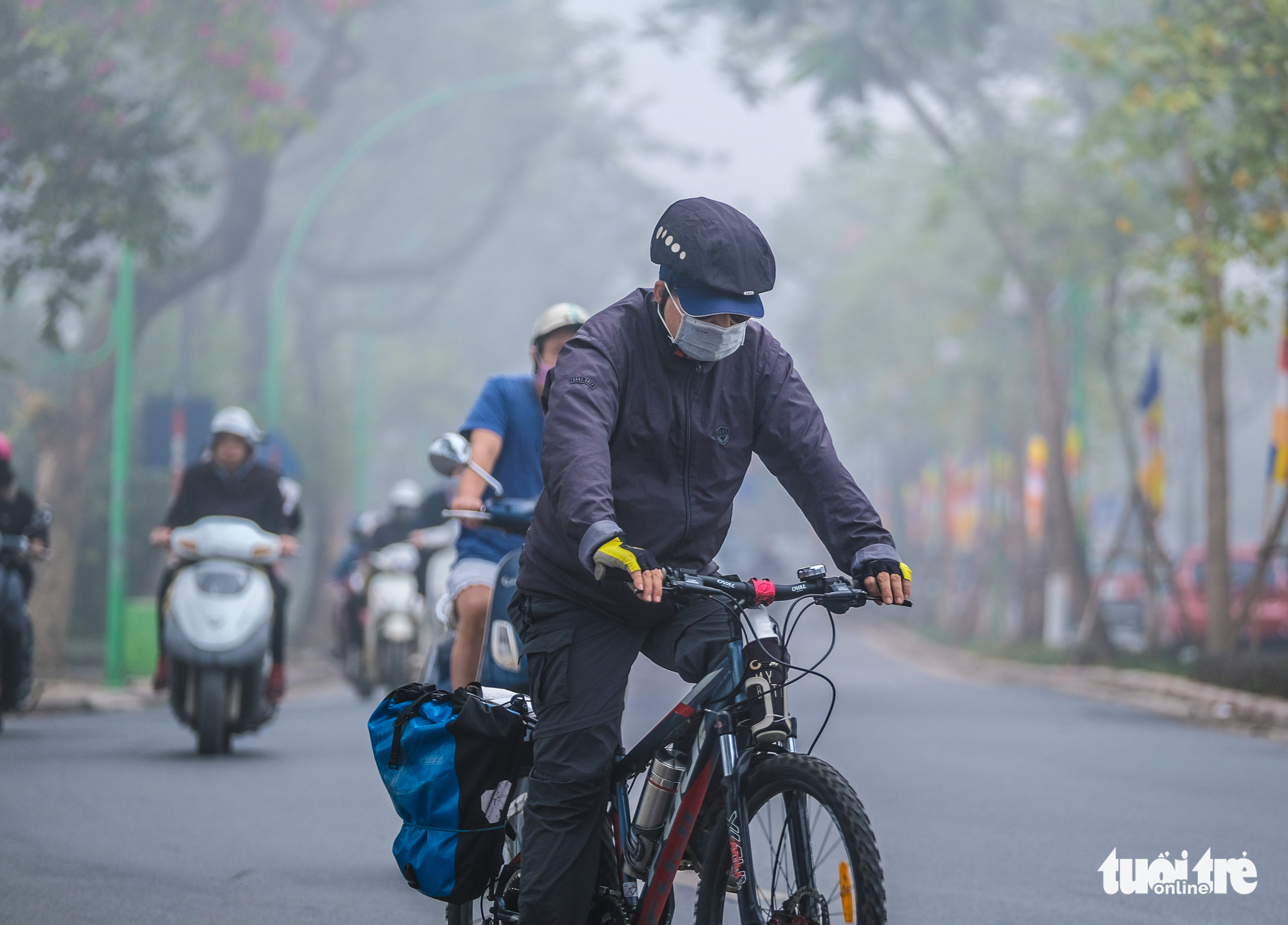 A cyclist is dressed in warm clothes in Hanoi on December 24, 2019.